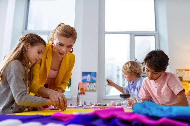 Schullehrer. grundschullehrer mit gelber jacke hilft den schülern beim ausschneiden
