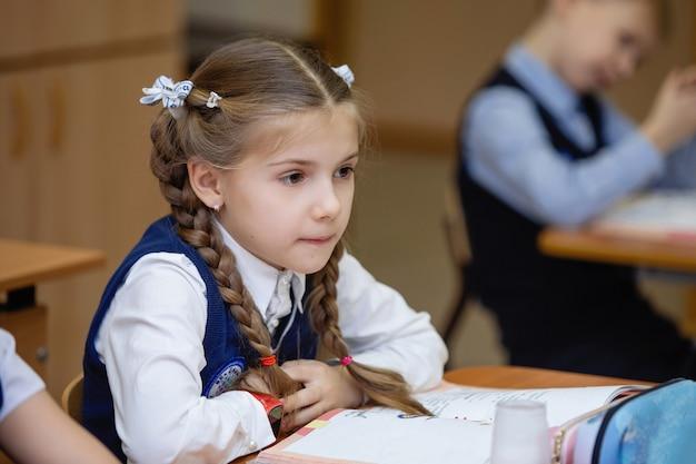 Schulmädchen an ihrem schreibtisch im klassenzimmer während des unterrichts. grundschulbildung. selektiver fokus.
