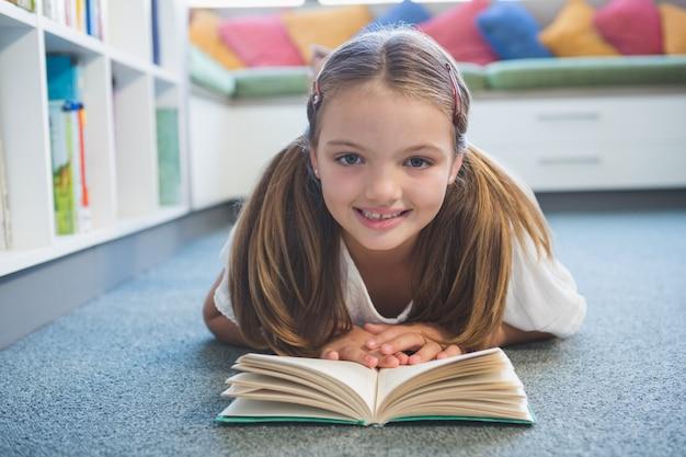 Schulmädchen auf dem boden liegend und ein buch in der bibliothek lesend
