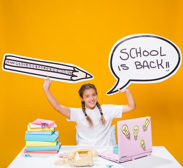 Schulmädchen auf schreibtisch mit laptop in der memphis-art