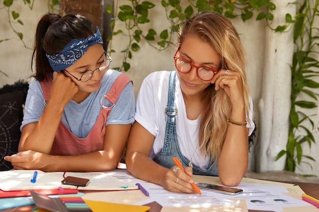 Schulmädchen bereiten sich auf wichtige prüfungen am college vor und unterstreichen informationen für die kursarbeit