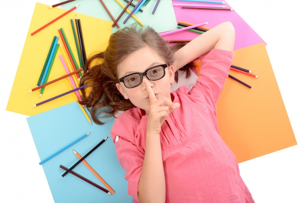 Schulmädchen, das auf dem boden mit farbbleistiften liegt