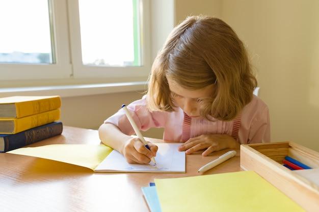 Schulmädchen, das bei tisch mit büchern sitzt und in notizbuch schreibt