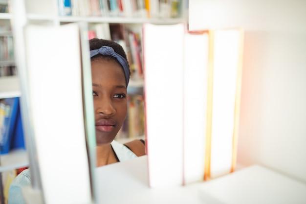 Schulmädchen, das buch vom bücherregal in der bibliothek auswählt