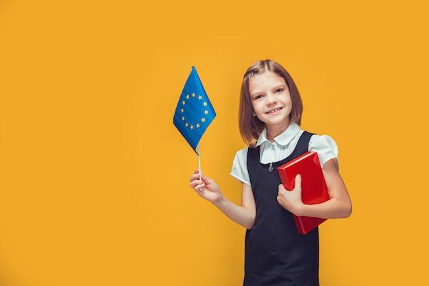 Schulmädchen, das die flagge der europäischen union und das buch in ihren händen hält bildung im europäischen konzept