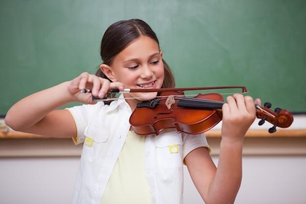 Schulmädchen, das die violine spielt