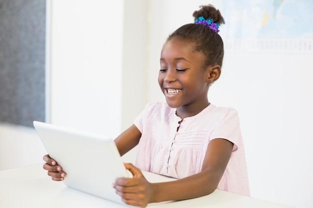 Schulmädchen, das digitale tablette im klassenzimmer verwendet