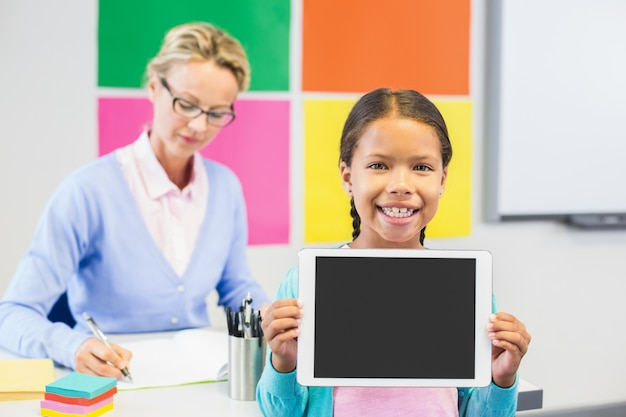Schulmädchen, das digitales tablett im klassenzimmer hält