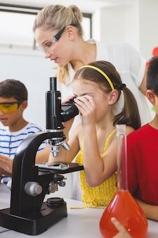 Schulmädchen, das durch mikroskop im labor schaut