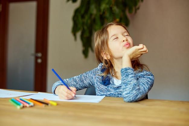 Schulmädchen, das ein bild mit buntstiften zeichnet und schreibt, mit buntstiften am tisch zu hause
