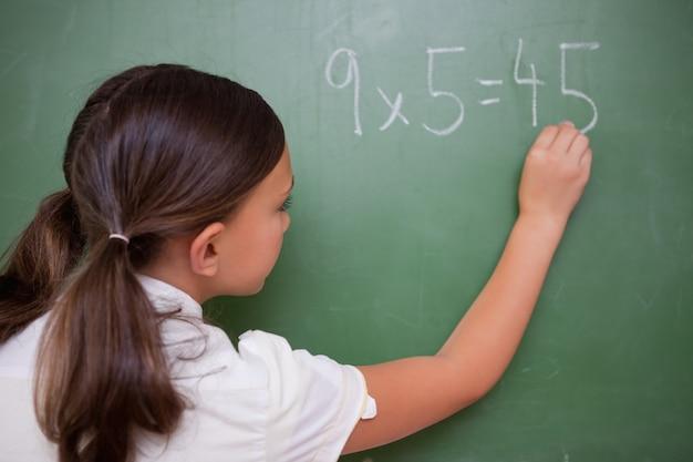 Schulmädchen, das ein ergebnis schreibt
