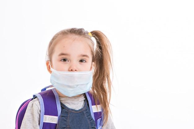 Schulmädchen, das eine gesichtsmaske auf einem weißen hintergrund trägt.