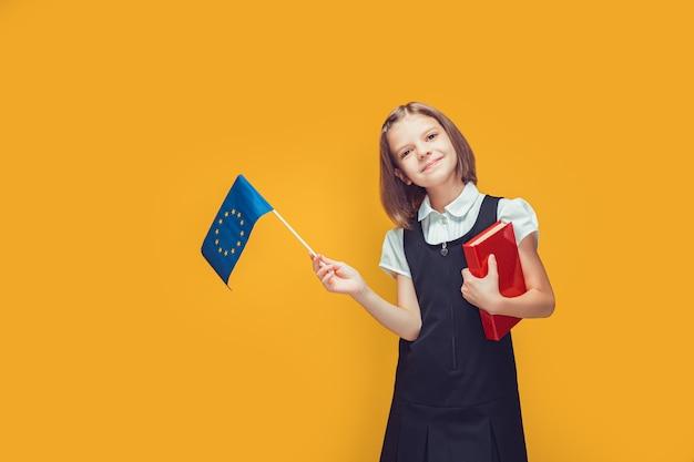 Schulmädchen, das eine kleine flagge der europäischen union und ein buch in ihren händen hält bildung im europäischen konzept