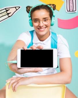 Schulmädchen, das eine smartphoneschablone darstellt