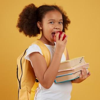 Schulmädchen, das einen apfel isst und bücher hält