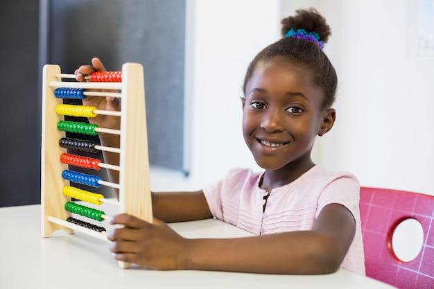 Schulmädchen, das einen mathe-abakus im klassenzimmer verwendet