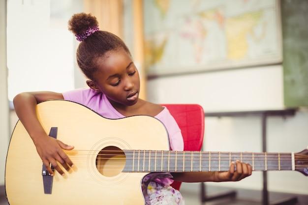 Schulmädchen, das gitarre im klassenzimmer spielt