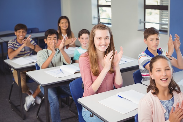 Schulmädchen, das hände im klassenzimmer in der schule klatscht