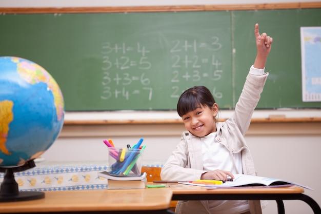 Schulmädchen, das ihre hand anhebt, um eine frage zu beantworten