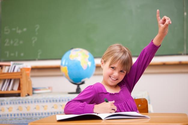 Schulmädchen, das ihre hand anhebt, um eine frage zu stellen