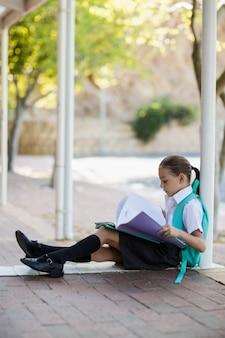 Schulmädchen, das im korridor sitzt und bücher liest