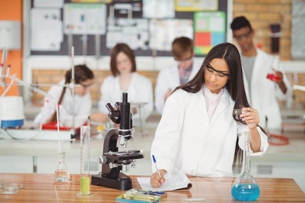 Schulmädchen, das im tagebuch schreibt, während im labor experimentiert wird