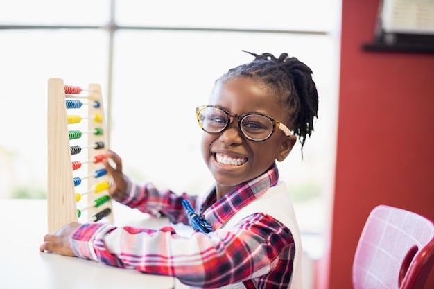 Schulmädchen, das in der schule einen mathe-abakus verwendet