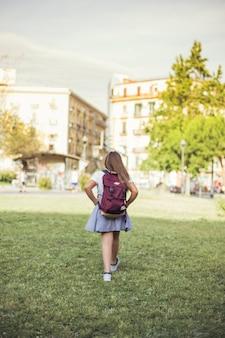 Schulmädchen, das in stadtpark geht