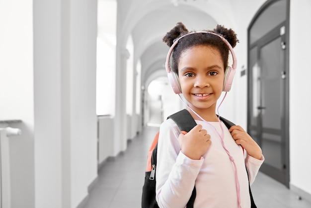 Schulmädchen, das kopfhörer trägt, die am korridor stehen