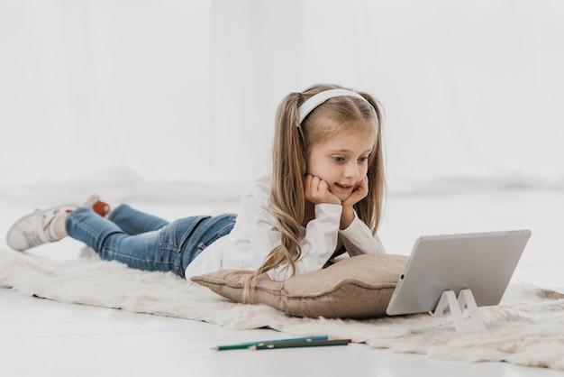 Schulmädchen, das kopfhörer trägt und online-klassen besucht
