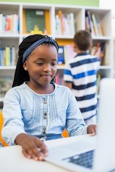 Schulmädchen, das laptop in der bibliothek verwendet