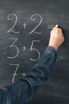 Schulmädchen, das mathe-summen in kreide auf tafel schreibt Premium Fotos