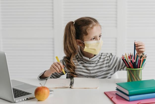 Schulmädchen, das medizinische maske und zeichnung trägt