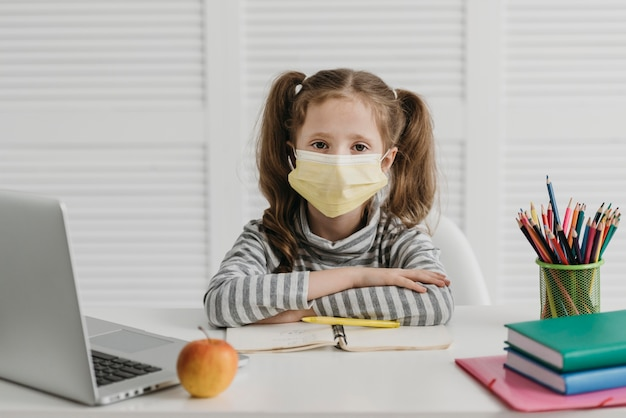 Schulmädchen, das medizinische maskenvoransicht trägt