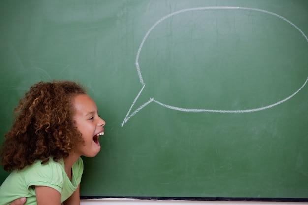 Schulmädchen, das mit einer spracheblase aufwirft