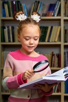 Schulmädchen, das mit enzyklopädie in der bibliothek steht, ein buch liest, neue informationen für gehirn erhält