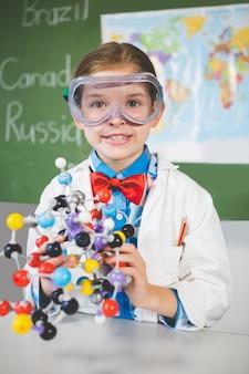 Schulmädchen, das molekülmodell für wissenschaftliches projekt im labor zusammenbaut