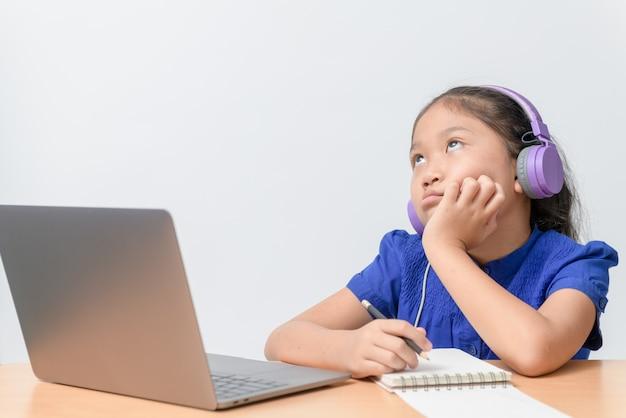 Schulmädchen, das online-bildungsklassen beobachtet, die sich zu hause gelangweilt und deprimiert fühlen.