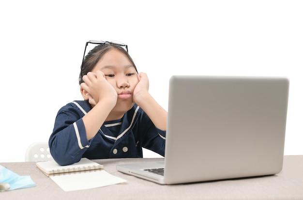 Schulmädchen, das online-bildungsklassen lernt, die sich auf weißem hintergrund gelangweilt und deprimiert fühlen, aufgrund des ausbruchs von covid 19 und des bildungskonzepts