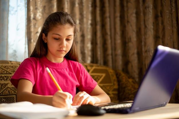 Schulmädchen, das online-unterricht mit laptop besucht