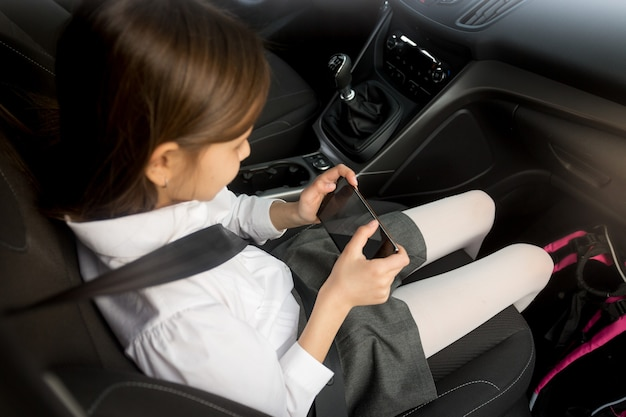 Schulmädchen, das smartphone benutzt, während es mit dem auto zur schule geht