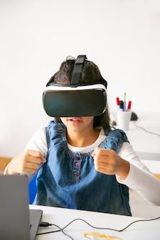 Schulmädchen, das spiel spielt und vr-headset verwendet