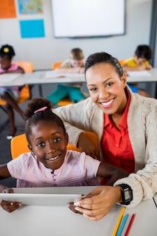 Schulmädchen, das tablette am schreibtisch mit ihrem lehrer verwendet