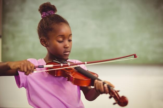 Schulmädchen, das violine im klassenzimmer spielt