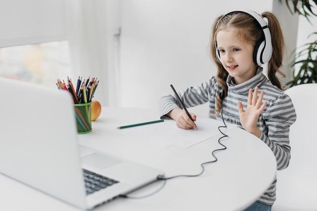 Schulmädchen, das virtuelle schule der kopfhörer trägt