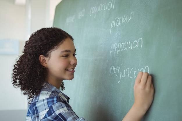 Schulmädchen, das vorgibt, lehrerin im klassenzimmer zu sein