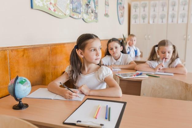 Schulmädchen, das weg schreibt und schaut