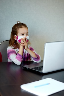 Schulmädchen, das zu hause mit einem notizbuch lernt und hausaufgaben macht.