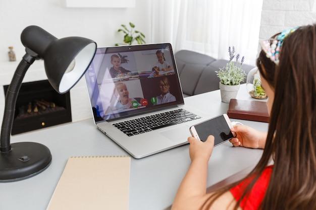 Schulmädchen, das zu hause mit laptop studiert. heimschule, online-bildung, heimunterricht, quarantäne-konzept - image