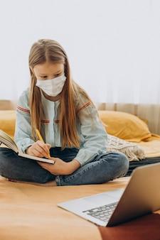 Schulmädchen, das zu hause studiert maske, fernes lernen